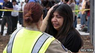 A women is comforted by a traffic officer near a college following a shooting on the campus in Santa Monica, California, on 7 June 2013