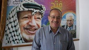 Faisal Abu Shahla stands in front of a Fatah poster in his office in Gaza City