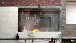 Egyptians look on as a mob attacks Shia Muslim men gathered in a house