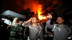 Police officers and soldiers outside Tanjung Gusta prison, set ablaze by inmates during a prison riot in Medan, North Sumatra, Indonesia on 11 July 2013