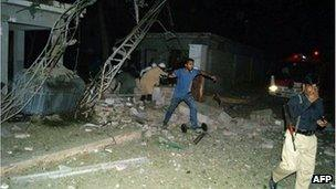 Pakistani security members are pictured at the site of suicide car bombing in the southern city of Sukkur on 24 July