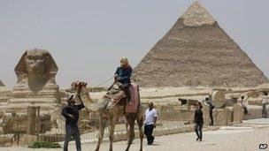 A tourist takes a camel ride at the Giza Pyramids in Giza, Egypt (May 2013)