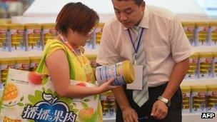 Woman looks at milk at a trade show in Shanghai