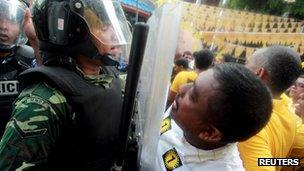 A supporter of Mohamed Nasheed shouts slogans in front of a police officer during a protest in Male on 27 September