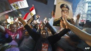 Crowd celebrates in Cairo's Tahrir Square with Egyptian flags and a sign of General Abdul Fattah al-Sisi on 3 July