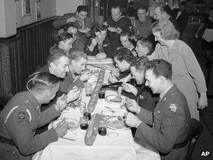 Anita O'Mera, of the staff of the Stage Door canteen, serves the wine to U.S. Army, Navy and Canadian Army men while Joe, the boss of Colucci's hands around the spaghetti and pizzeria in New York on Dec. 26, 1942.