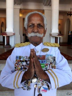 In this photograph taken on February 6, 2010, Sri Lanka's legendary doorman, Kottarapattu Chattu Kuttan holds his palms in a traditional greeting, outside the island's historic 146-year-old Galle Face Hotel in Colombo.