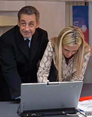 Nicolas Sarkozy votes next to an unnamed woman at a laptop in Paris, 29 November