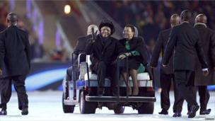 Nelson Mandela sits next to his wife Graca Machel as he greets fans during the closing ceremony of the 2010 World Cup at Soccer City stadium in Johannesburg July 11, 2010.