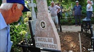 Romanians look at the tomb of Nicolae Ceausescu at the Ghencea cemetery in Bucharest, 21 July 2010