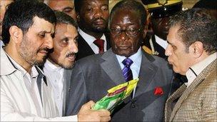 Mahmoud Ahmadinejad (l) and Robert Mugabe (c) inspect produce at a trade fair