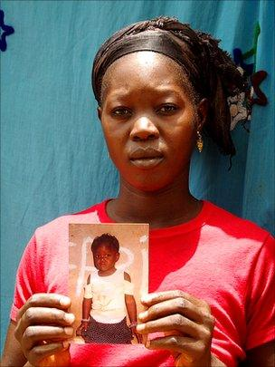Hawa Camera holding a photo of her daughter who is missing