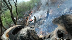 Pakistani rescue workers search for survivors at the crash site