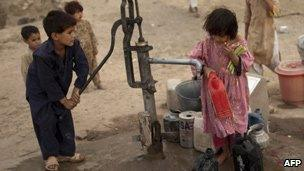 Pakistani children pump water from a well in the capital, Islamabad - 21 June 2010