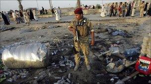 An Iraqi soldier stands guard at the site of a bomb attack in Kerbala, 27 July 2010
