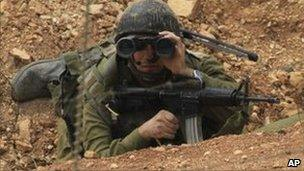 Israeli soldier uses binoculars near the disputed border area with Lebanon, August 4, 2010.