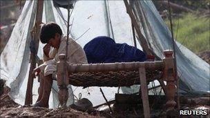 A boy sit on a bed in ruin on family home in Pabbi, north-west Khyber Pakhtunkhwa province, on 5 August 2010