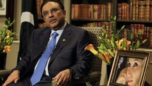 Asif Ali Zardari speaks to journalists with a picture of his late wife Benazir at his side