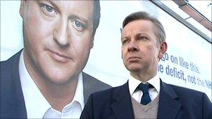 Michael Gove walking past campaign poster of David Cameron