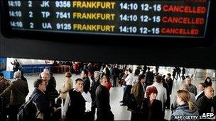People stand in front of an information board in the departure hall of Sofia airport