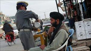 Policeman buys tea in Lashkar Gah in March 2010