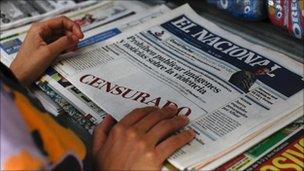 """A woman buys a copy of El Nacional, whose front page carried white boxes with the words """"censored"""" written in red (18 August 2010)"""