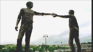 Statue of two men reaching out to each other.