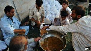 Pakistani men prepare food bags for flood-affected people in Sukkur (19 August 19 2010)