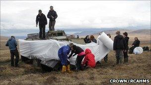 Children bubble wrap an APC at Cape Wrath. Image: Copyright Crown/RCAHMS