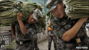 Chinese soldiers carry sandbags to shore up flood defences in Dandong.