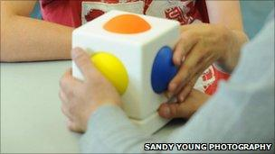 Child playing with a 'Skoog' musical cube