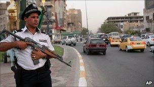 An Iraqi traffic policeman holds an AK-47 in central Baghdad, Iraq, Aug 2010