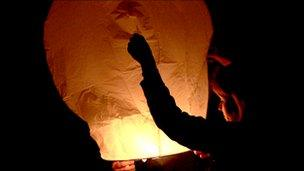 A woman holds a sky lantern as it is being launched