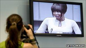 A photographer takes a picture of Naomi Campbell on screen