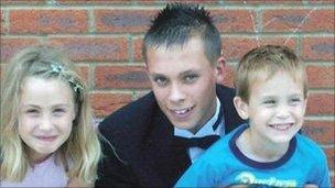 Joshua Parkin, centre, with his sister and one of his brothers