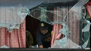 A Philippine forensic expert examines the bus in Manila on 24 August 2010