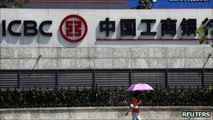 A woman carrying an umbrella walks past an office building that includes a China Telecom office and a branch of the Industrial and Commercial Bank of China in central Beijing