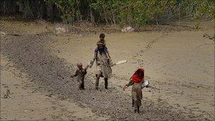 A man wades with his children through flood mud in Nowshera, 20 August, 2010