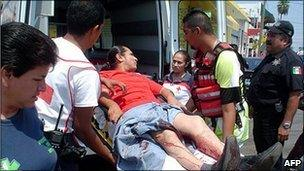 An injured man is taken onto an ambulance in Reynosa, Mexico