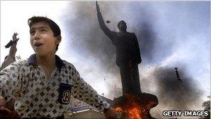 A boy cheers in front of a statue of Saddam Hussein that was set on fire on 12 April 2010