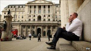 An office worker talks on a mobile phone outside the Bank of England