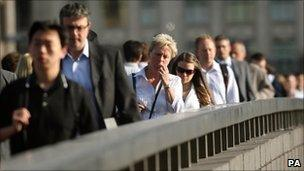 Commuters cross London Bridge on their way to work in the City financial district of London