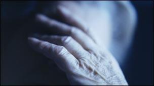 Elderly woman with her head in her hands