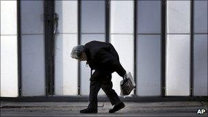 An elderly woman walks by a shrine in Tokyo