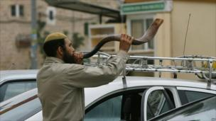 A Jewish settler blows the Shofar horn on the eve of Yom Kippur, near the disputed Ibrahimi mosque, known to Jews as the Tomb of the Patriarchs, during the weekly Muslim Friday prayer in the flashpoint West Bank city of Hebron on 17 September 2010.
