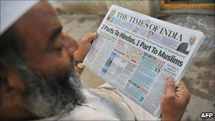 Muslim man reading newspaper with Ayodhya headlines