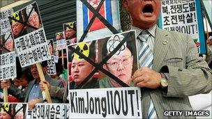 South Korean protesters hold portraits of North Korean leader Kim Jong-il and his son
