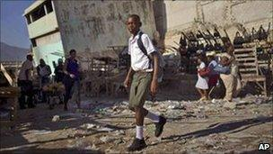 A student walks past damaged buildings in Haiti's capital Port-au-Prince. Photo: October 2010