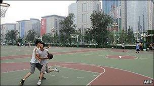 Chinese youths play basketball in a street court in Beijing
