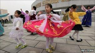 Women and children dance at the Party Foundation Monument in the North Korean capital of Pyongyang,